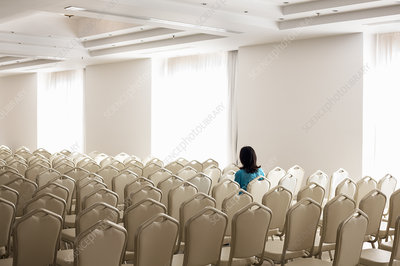 Solitary woman amongst empty chairs