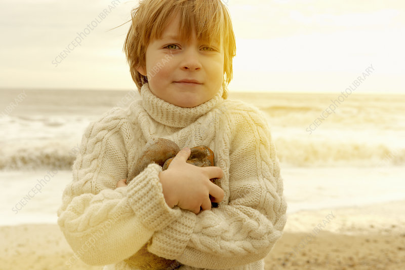 Young boy on a beach holding stones