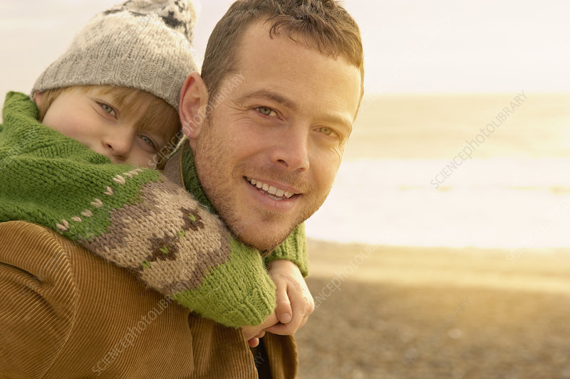 Man carrying young boy on beach. Autumn