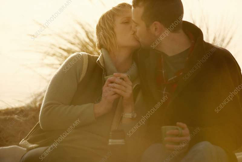 Couple outdoors kissing. With coffee