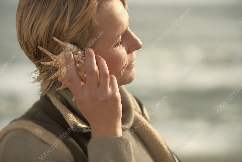 Woman by sea, listening in seashell