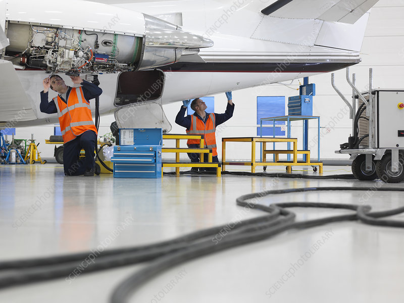 Engineers work on jet aircraft