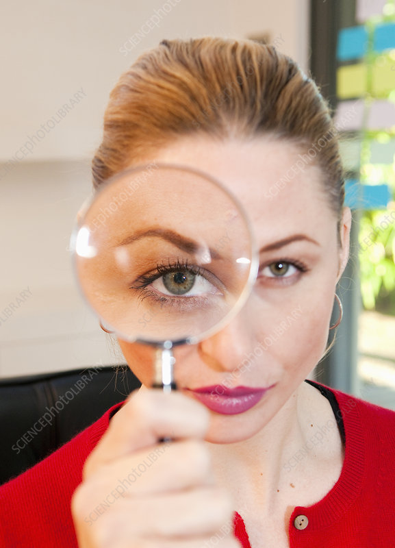 Woman looks thru magnifying glass