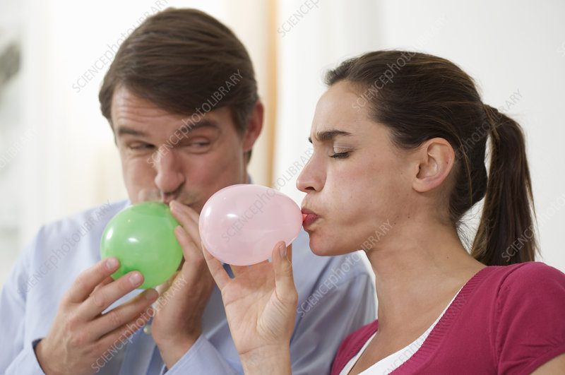 a couple trying to blow balloons