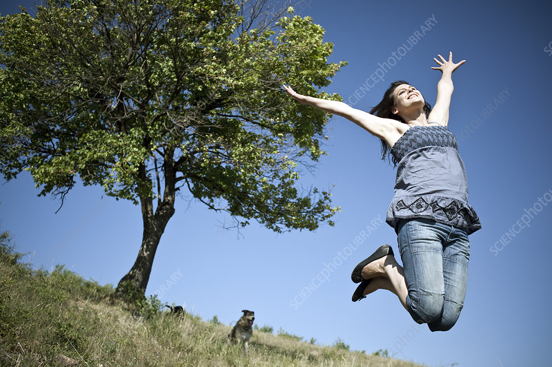 Woman leaping by tree
