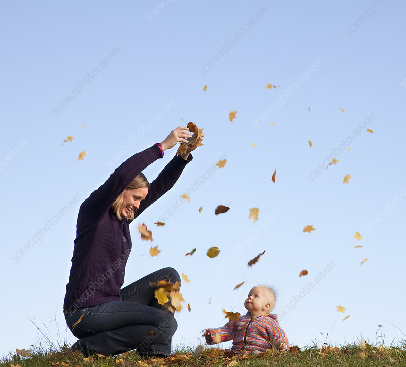 mother and baby throwing autumn leaves