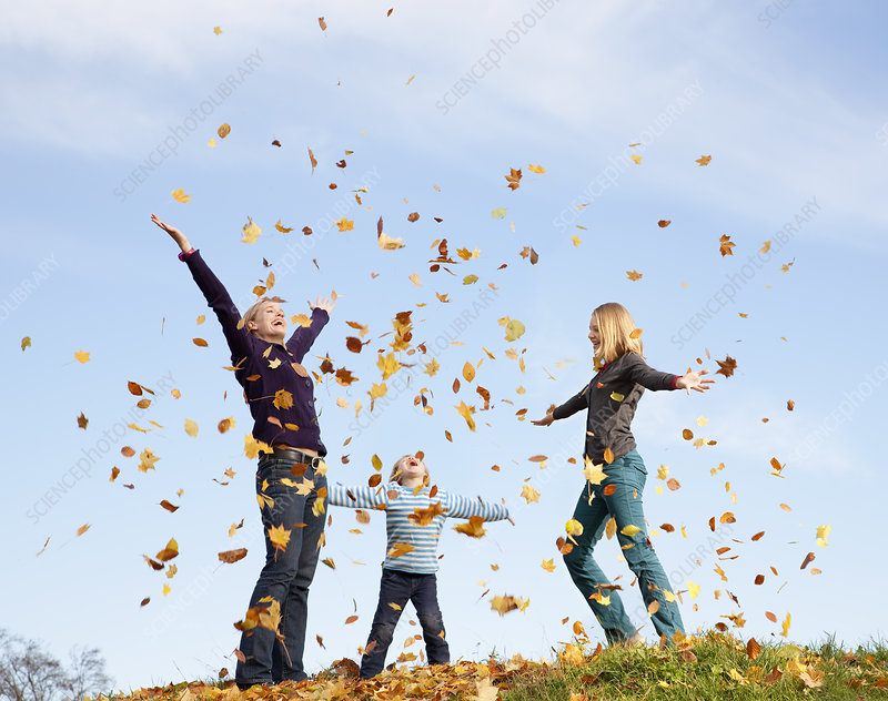 woman, boy and girl throw autumn leaves