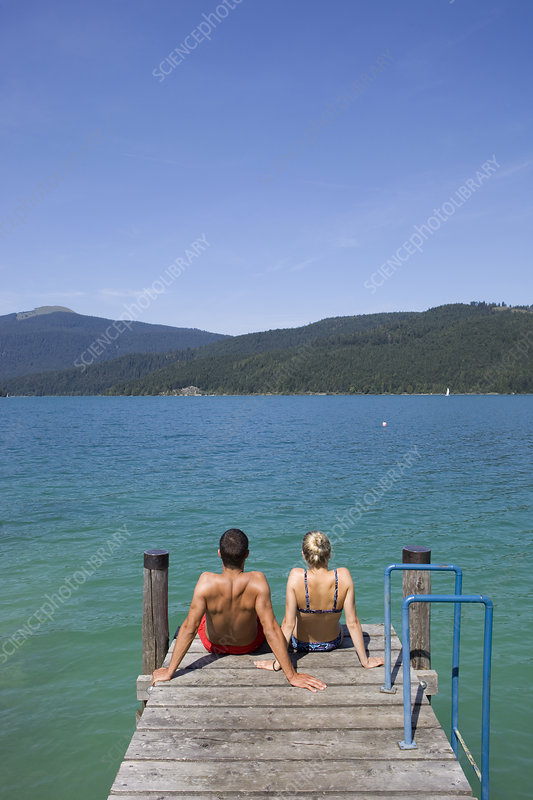 A couple sitting on a pier by a lake