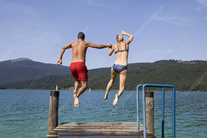 A couple jumping into the water