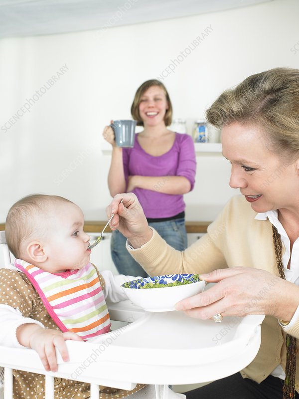 Grandmother feeding baby