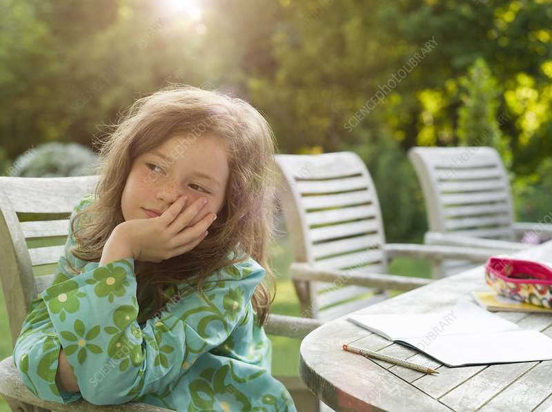 Young girl daydreaming in garden