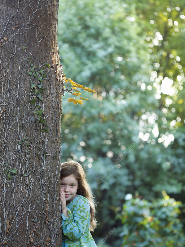 Young girl leaning on tree in garden