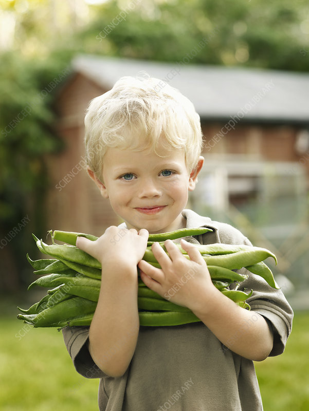 young boy holding garden produce outside