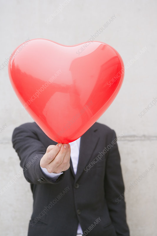 man in suit holding a heart balloon