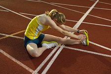 female athlete stretching leg muscles