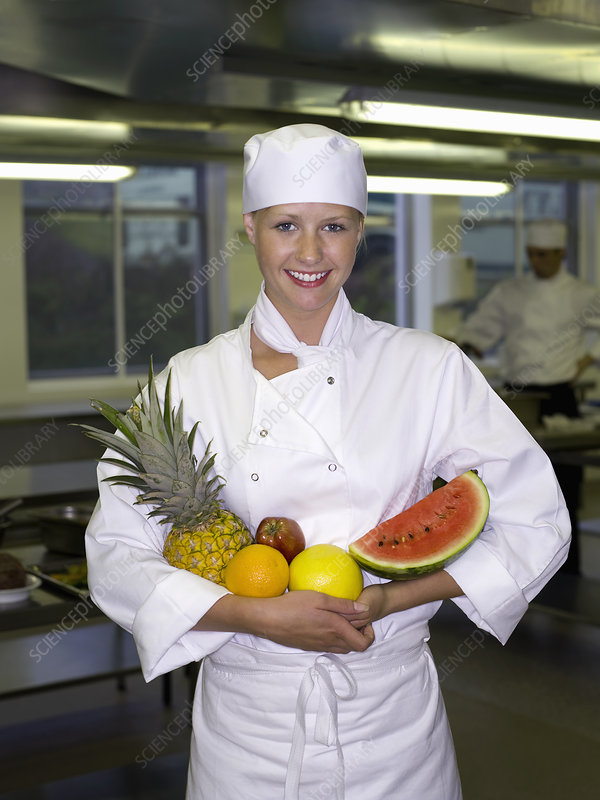 Portrait of a female chef holding fruit