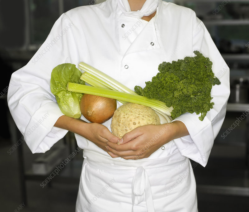 A chef holding some vegetables