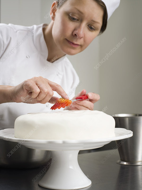 A female chef cake decorating