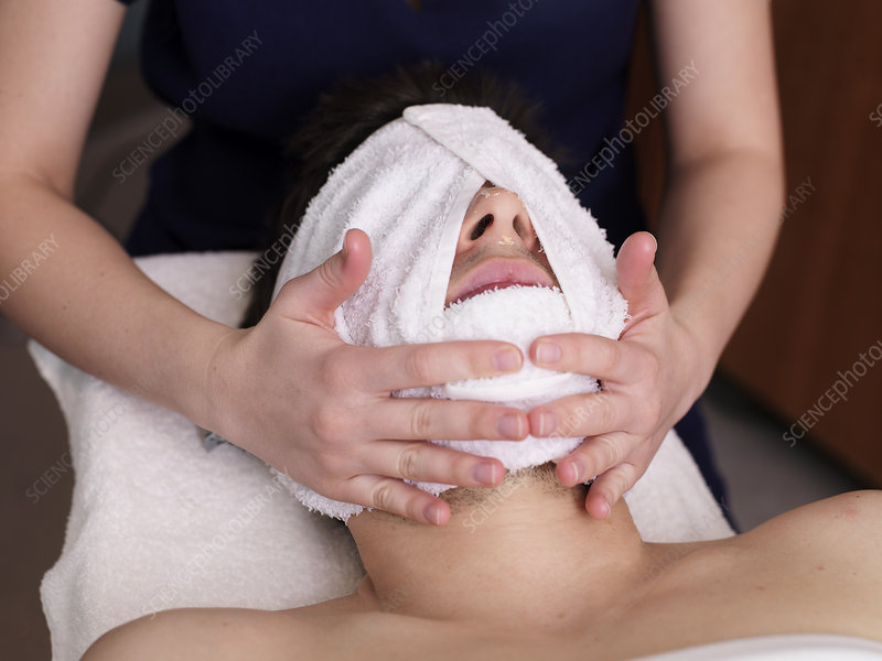 Man receiving massage to face