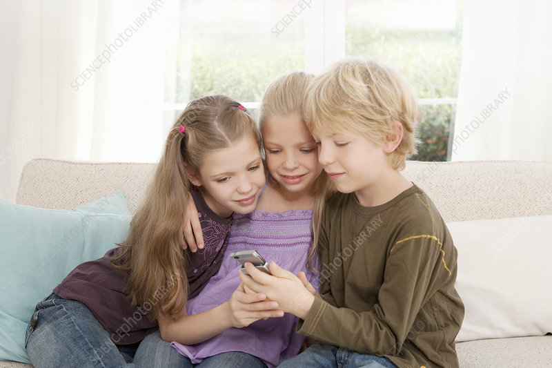 Three children looking at a mobile phone