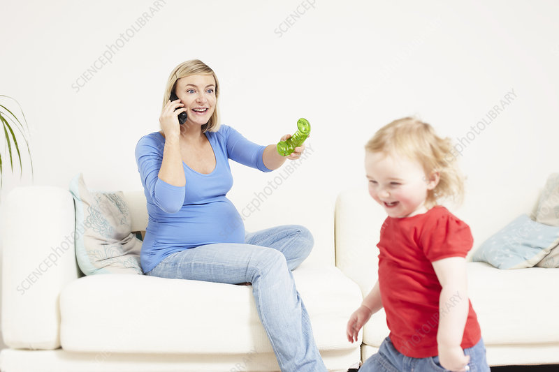 Pregnant woman on phone with toddler