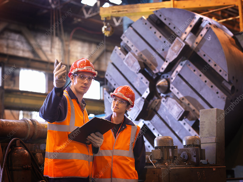Male & Female Steel Engineers In Factory