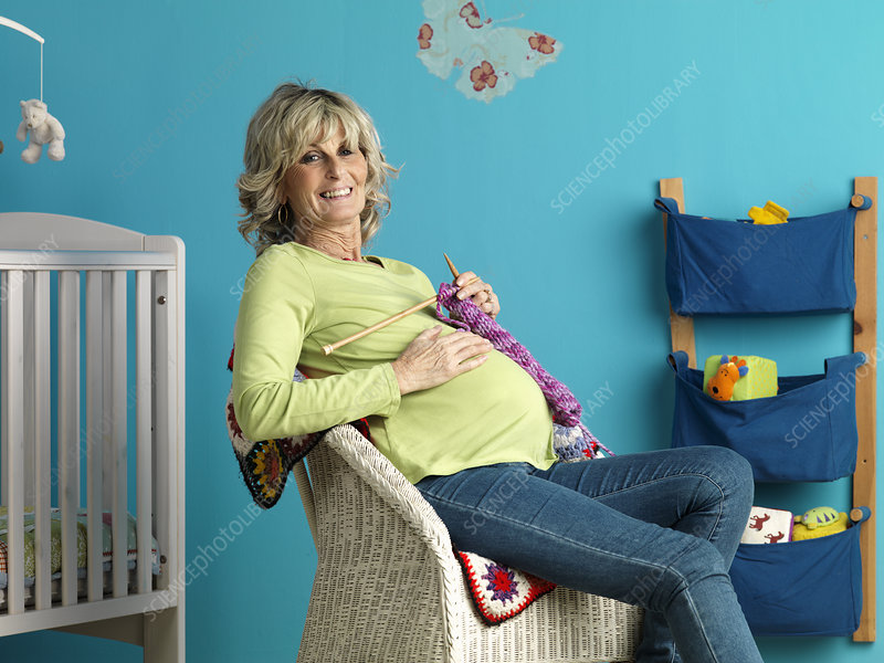 Pregnant mature woman knitting