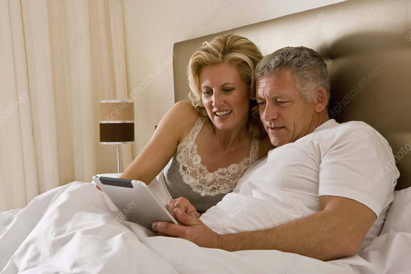 Couple in bed using tablet computer