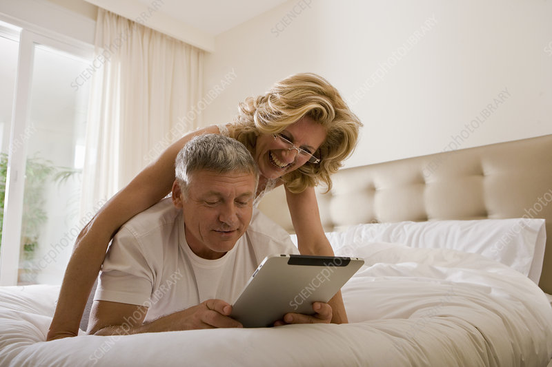 Couple looking at tablet computer in bed