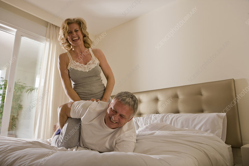 Mature couple wrestling on bed