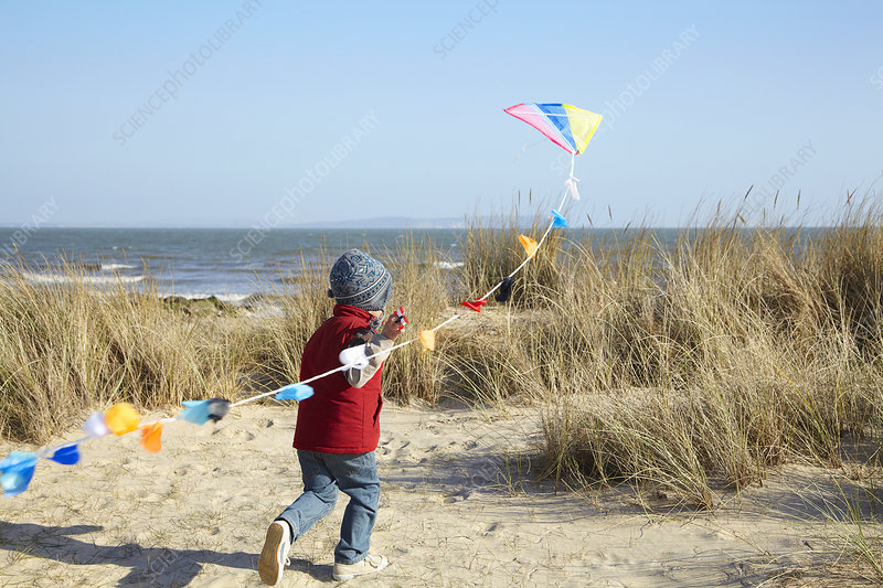 Young boy running towards sea with kite