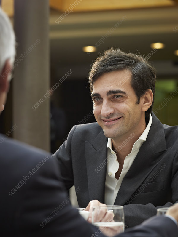 Close up of smiling man in a group meetin