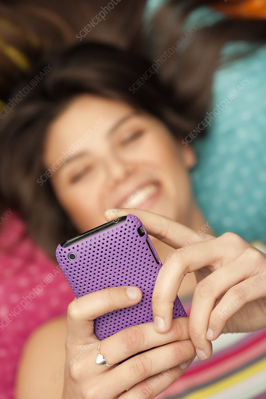 Young woman checking her phone, smiling