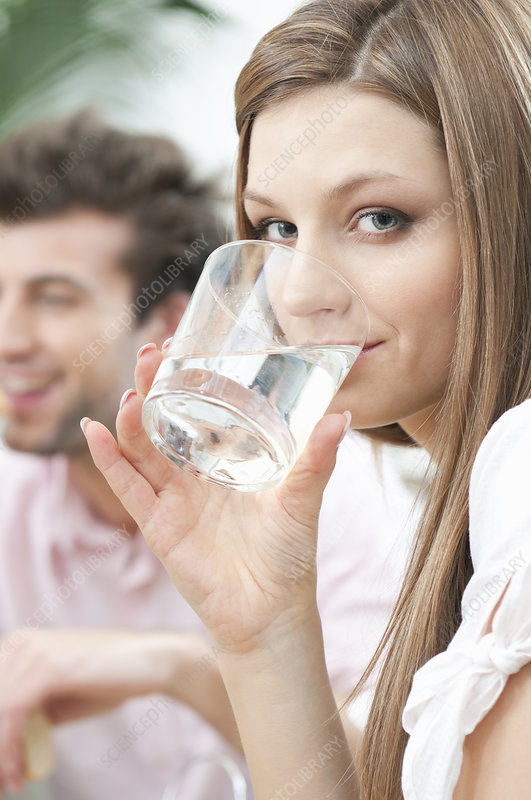 Girl drinking glass of water at home