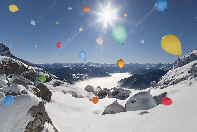 Balloons flying over winter landscape