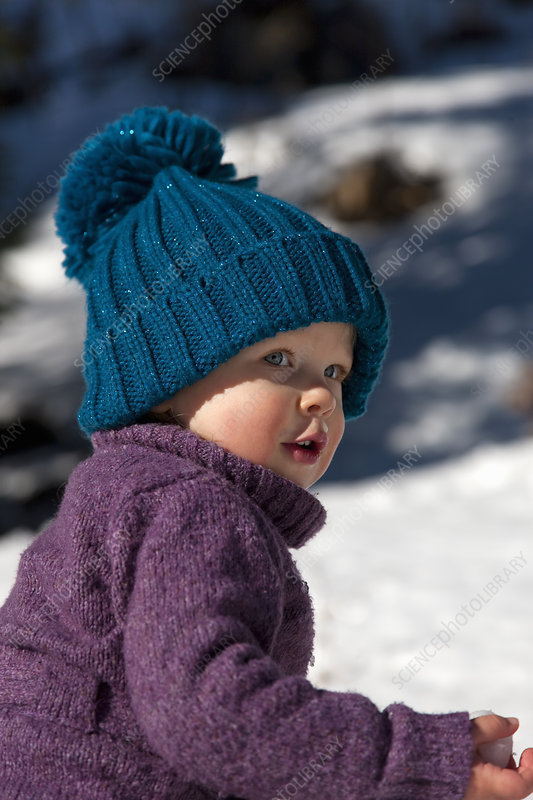 Little girl with big hat playing in snow