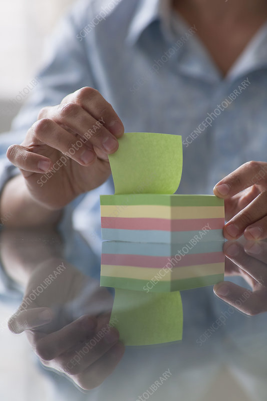 close up of a man picking up a post-it no