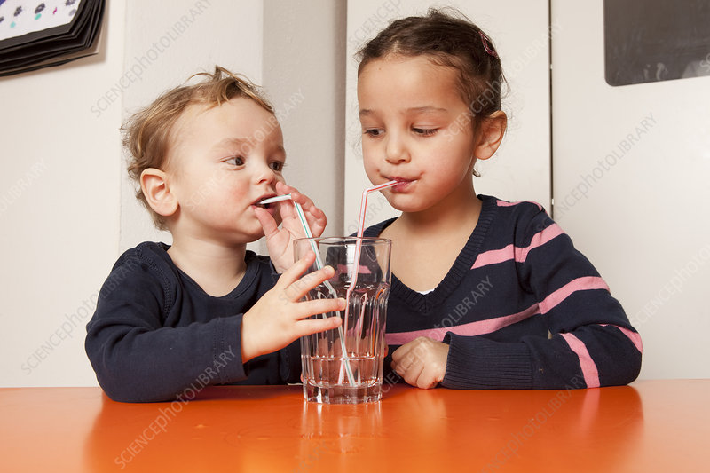 Boy and girl drinking water with straws
