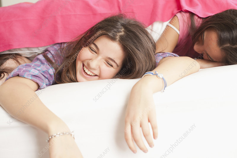 girls lying in bed laughing