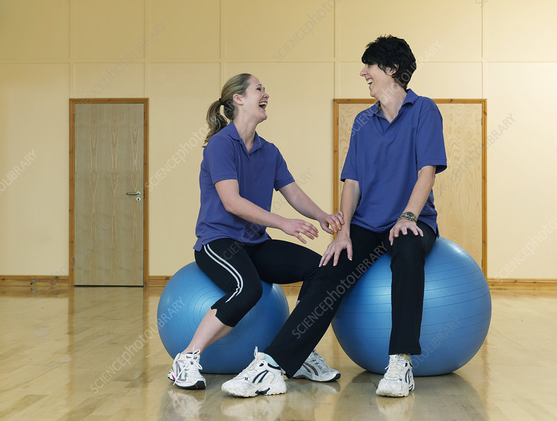 female gym instructors relaxing on balls