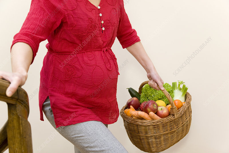 pregnant woman carrying fruit basket
