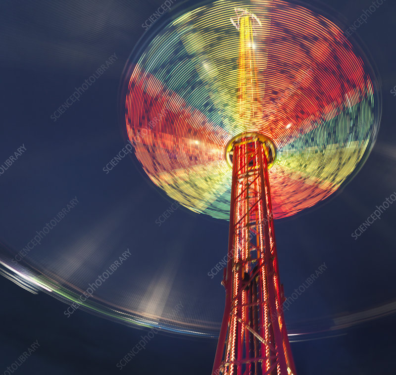 Illuminated chairoplane against dark sky