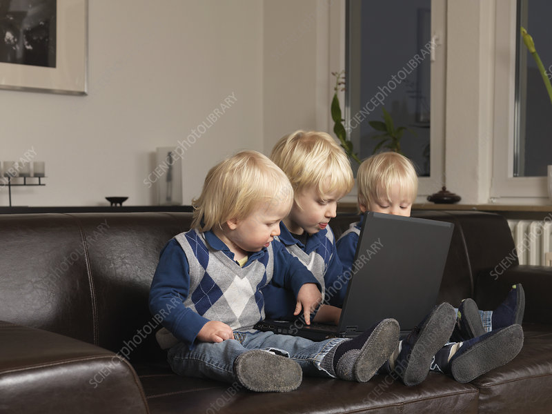 Three toddlers working on laptop