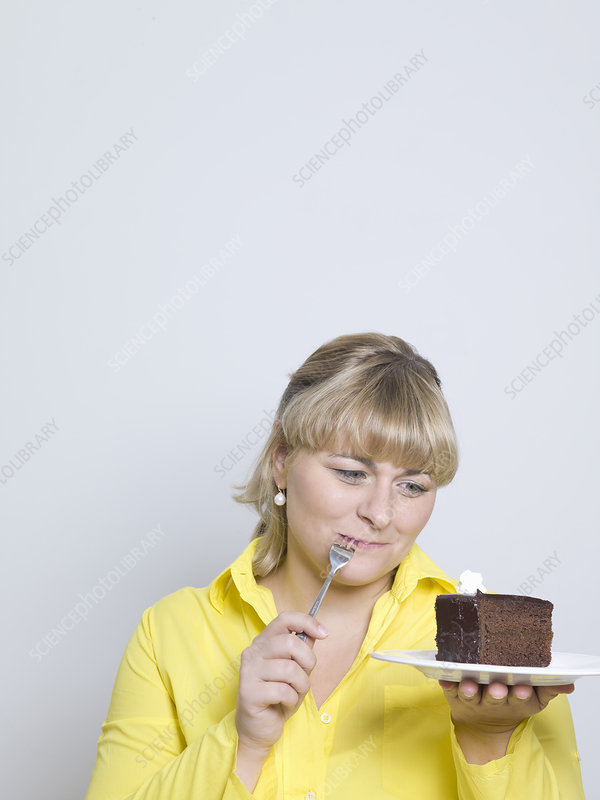woman looking at plate of cake
