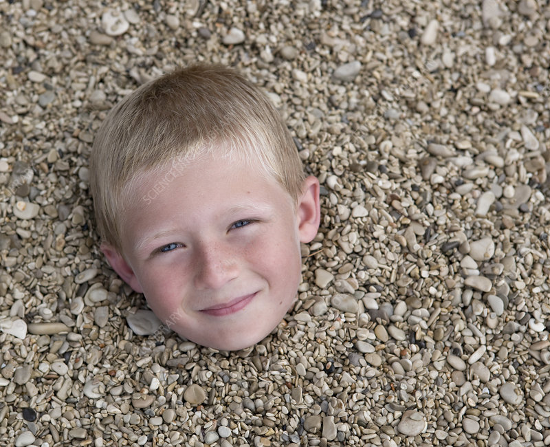 Boy buried in pebbles on beach