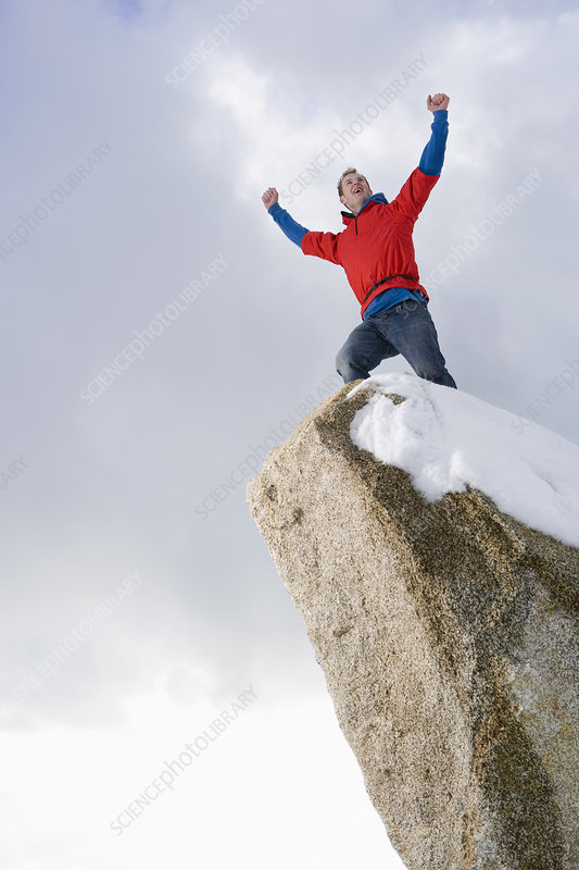 climber celebrating on snow capped peak