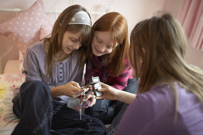 Teenage girls playing with mobile phones