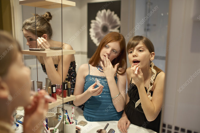 Teenage girls applying make-up