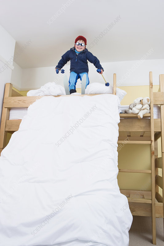 Boy with skis on bed