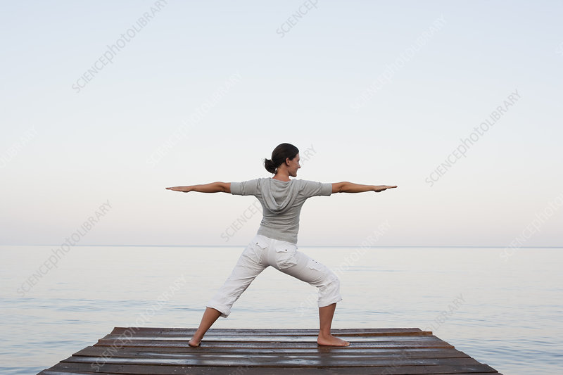 Young Woman Doing Yoga At Jetty